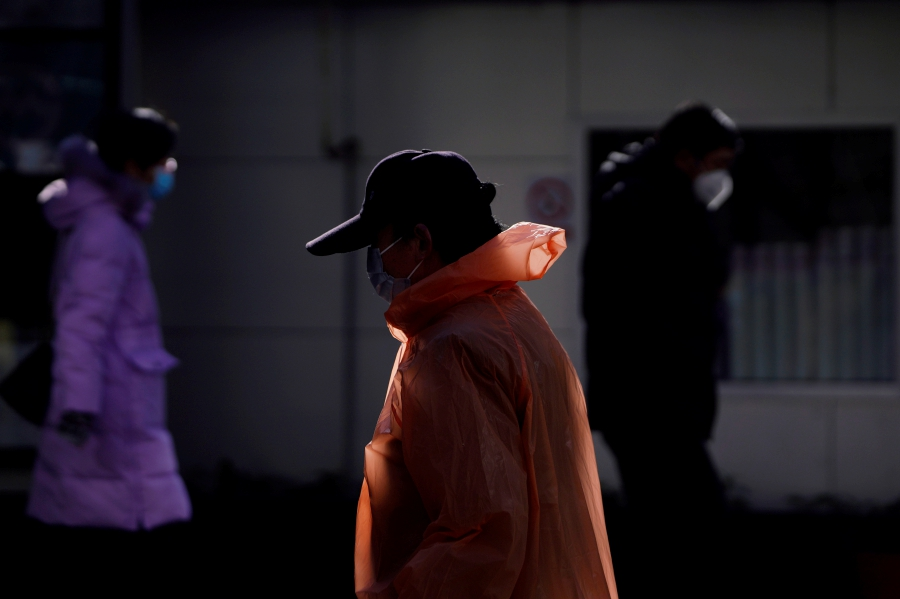 A pedestrian wearing a raincoat and face mask is seen on a street, as the country is hit by an outbreak of the novel coronavirus. - REUTERS