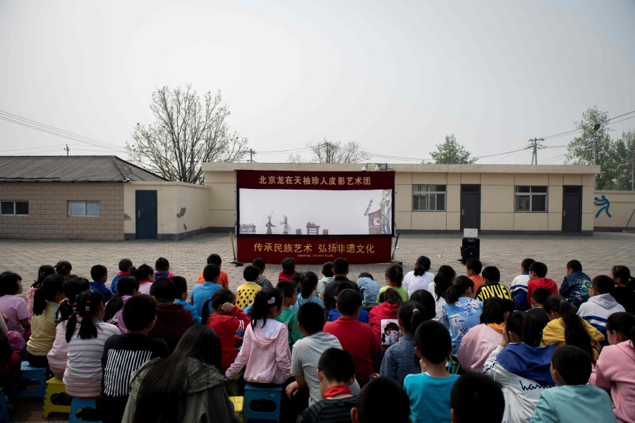 (File pix) In this picture taken on April 17, 2019, schoolchildren watch a shadow theatre performance conducted by Beijing Shadow Show Troupe puppeteers at a school sportsground on the outskirts of Beijing. AFP Photo