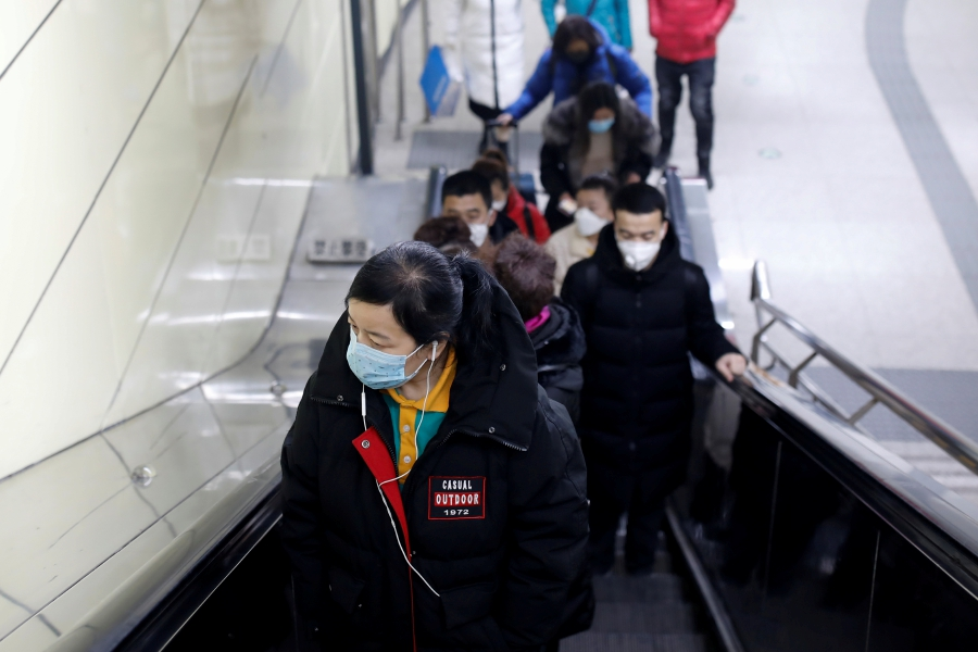 People wearing face masks are seen at the escalator of a subway station, as the country is hit by an outbreak of the new coronavirus, in Beijing, China January 27, 2020. - REUTERS/Carlos Garcia Rawlins