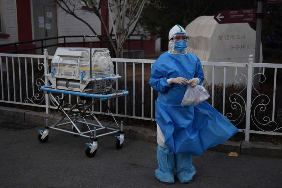 A medical worker wears protective clothing as a preventive measure against the COVID-19 coronavirus as she waits for a security guard to open a gate before moving an incubator between buildings at a hospital in Beijing on February 21, 2020. - An eruption of new virus cases in South Korea, Iran and Chinese hospitals and prisons rekindled concerns on February 21 about the spread of a deadly disease that has killed more than 2,200 people. (Photo by GREG BAKER / AFP)