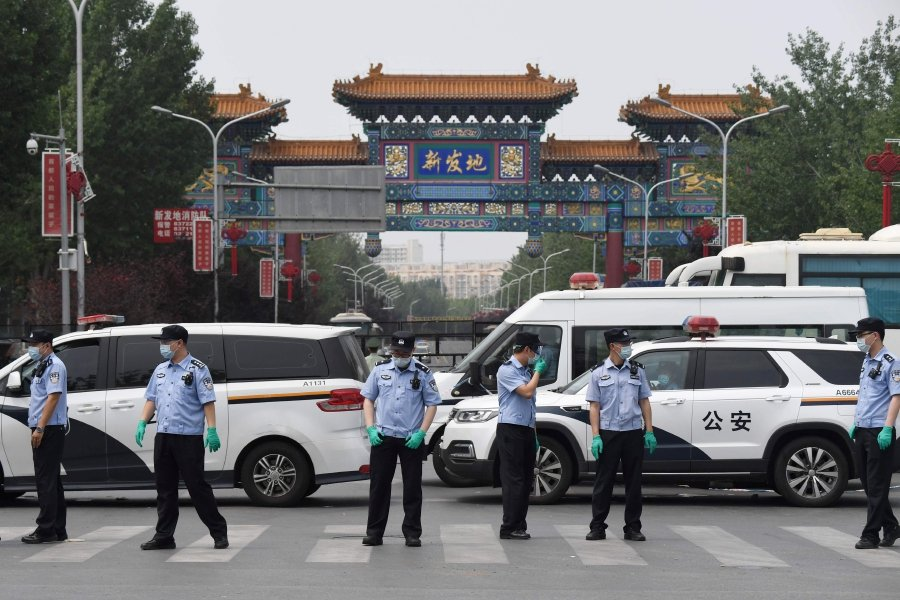 Chinese police guard the entrance to the closed Xinfadi market in Beijing on June 13, 2020. - Eleven residential estates in south Beijing have been locked down due to a fresh cluster of coronavirus cases linked to the Xinfadi meat market, officials said on June 13. (Photo by GREG BAKER / AFP)