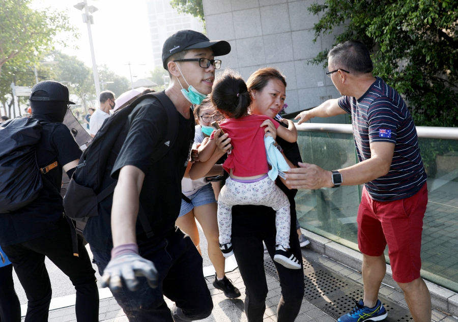 A woman runs with a child away from tear gas, which was fired by police in a children's park, during a pro-democracy rally against police brutality in Hong Kong, China, 27 October 2019. Hong Kong has witnessed months of mass protests, which were originally triggered by a now withdrawn extradition bill, and have since turned into a wider pro-democracy movement. - EPA/JEROME FAVRE