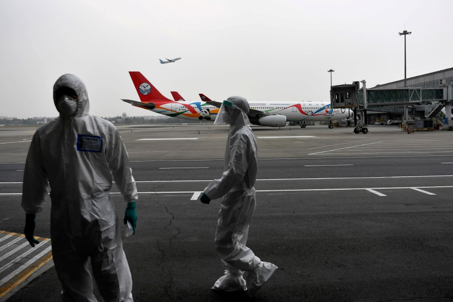 Customs officers in protective suits are seen near a Sichuan Airlines aircraft on the tarmac of Chengdu Shuangliu International Airport following a global outbreak of the coronavirus disease (COVID-19), in Chengdu, Sichuan province, China March 26, 2020. Picture taken March 26, 2020. - cnsphoto via REUTERS