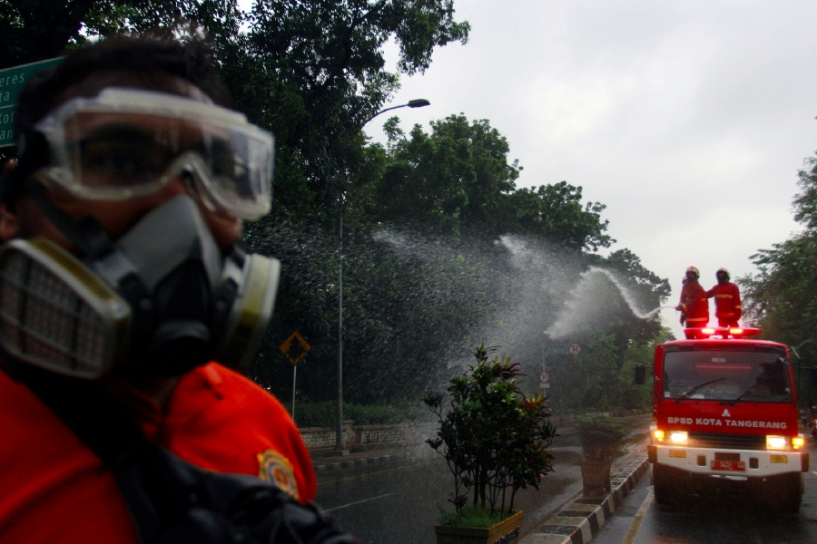 Firefighters spray disinfectant on the road, to prevent the spread of coronavirus disease (COVID-19) in Tangerang, near Jakarta, Indonesia March 21, 2020 in this photo taken by Antara Foto. Antara Foto/Muhammad Iqbal/ via REUTERS