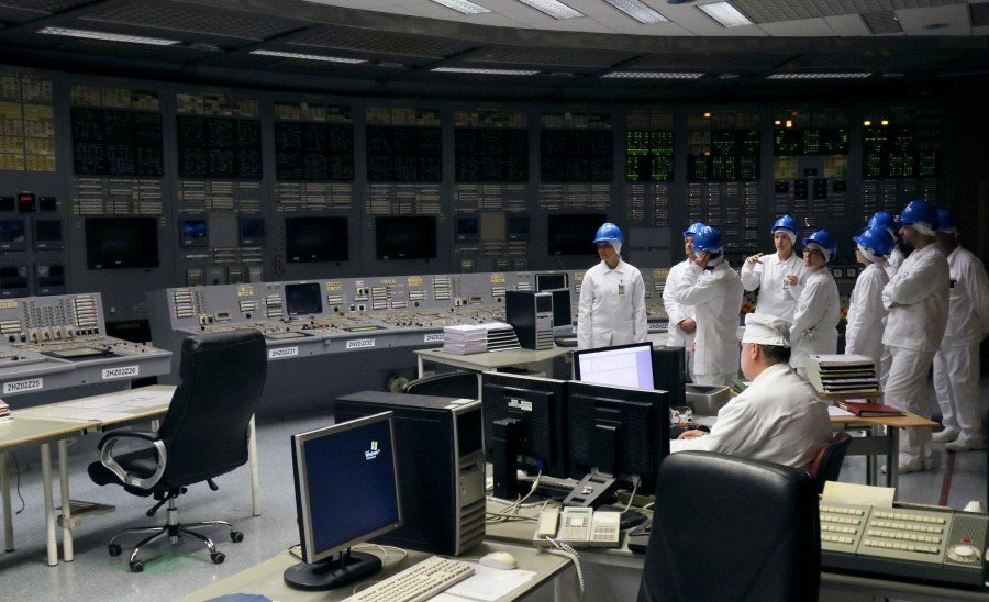 People stand in the monitoring room during a guided tour inside the inoperative Ignalina nuclear power plant in Visaginas, Lithuania. - AFP