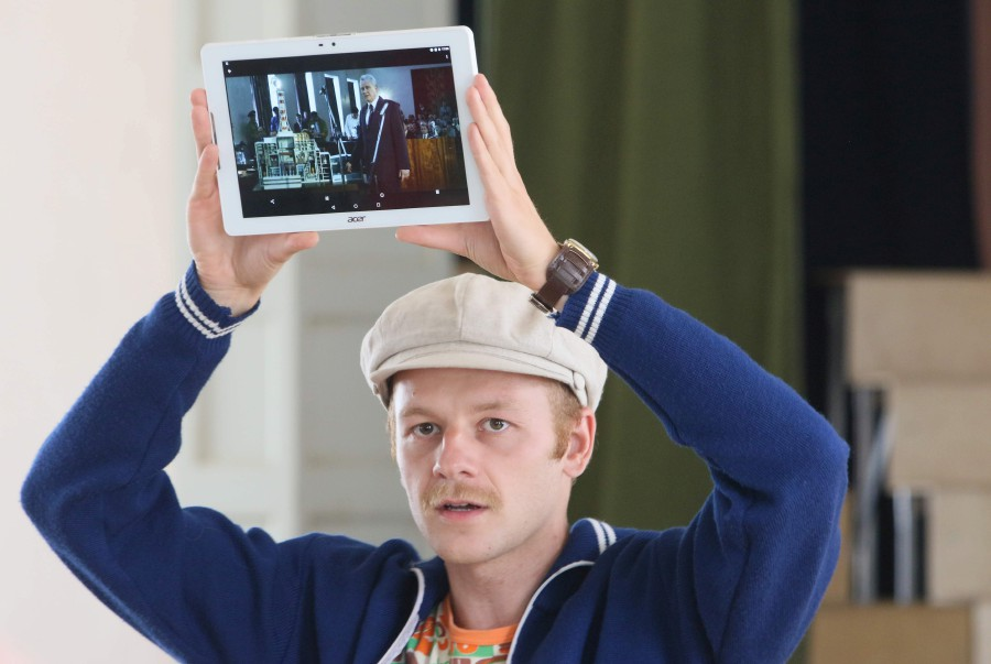 """The tour guide holds up a tablet showing a still of the HBO series """"Chernobyl"""" during a tour to the places where the series was shot in the district Fabijoniskes in Vilnius. - AFP"""
