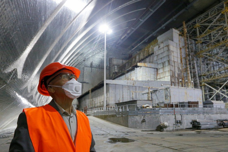 Ukrainian military pilot Mykola Volkozub looks on next to the old sarcophagus covering the damaged fourth reactor, under the New Safe Confinement (NSC) structure at the Chernobyl Nuclear Power Plant, in Chernobyl, Ukraine. - Reuters