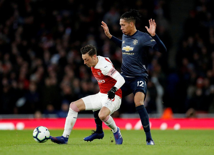 Arsenal's Mesut Ozil in action with Manchester United's Chris Smalling. - Reuters