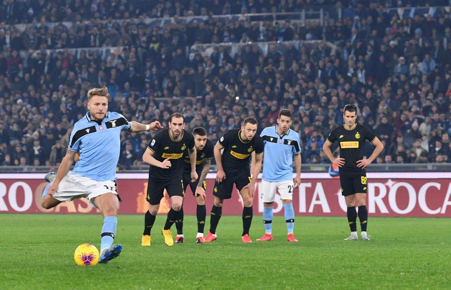 Lazio's Ciro Immobile (left) shoots to score a penalty against Inter Milan at the Olympic stadium in Rome. -AFP