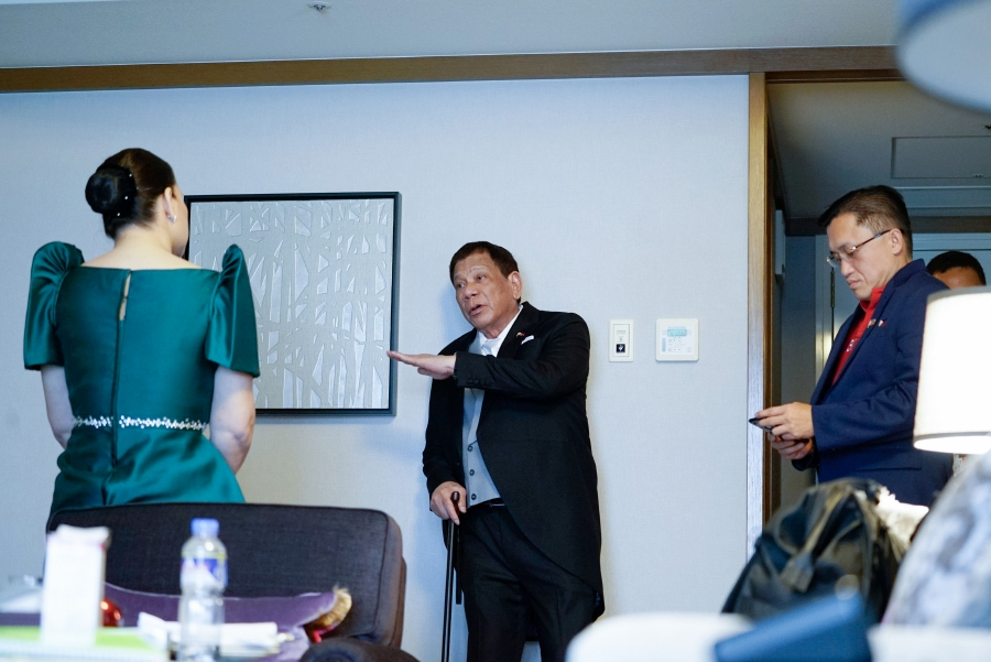 "In this handout photo taken and released by the Presidential Photographers Division (PPD) on October 22, 2019 shows Philippine President Rodrigo Duterte (C) holding a cane while speaking to his daughter, Davao City Mayor Sara Duterte-Carpio (L) while Senator Bong Go (R) listens before the enthronement ceremony of Japanese Emperor Naruhito, at a hotel in Tokyo. - President Duterte, suffering from ""unbearable pain"" in his spine, is cutting short a trip to Japan after attending Emperor Naruhito's enthronement, the Filipino leader's spokesman said October 22. (Photo by King RODRIGUES / Presidential Photographers Division / AFP)"