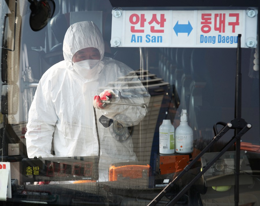 A worker from a disinfection service sprays disinfectant in a bus departing to Daegu as part of preventive measures against the spread of the COVID-19 coronavirus, at a bus terminal in Ansan, south of Seoul. -Yonhap/AFP