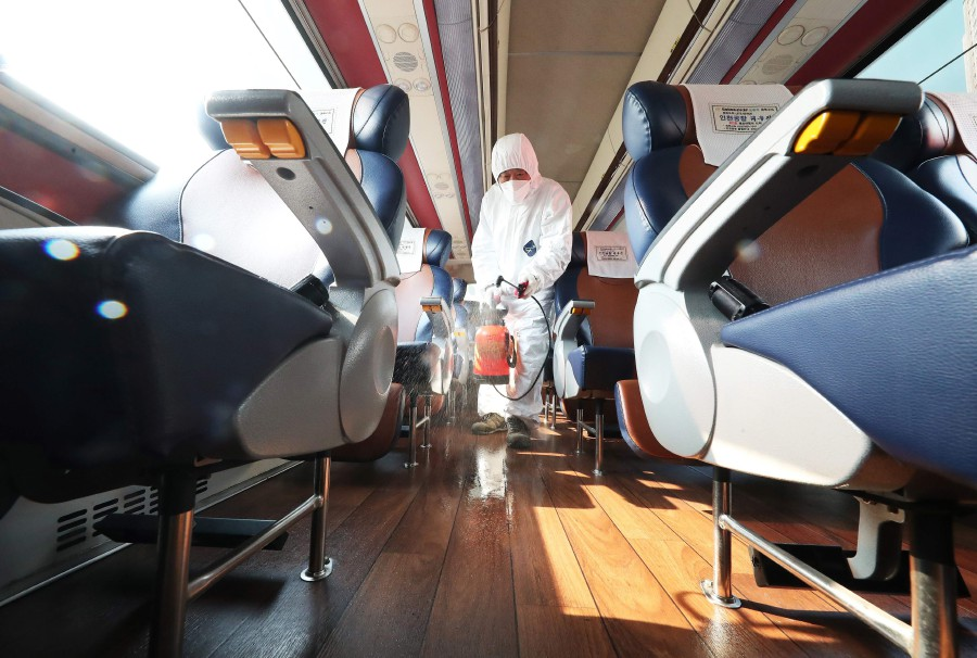 A worker from a disinfection service sprays disinfectant in a bus departing to Daegu as part of preventive measures against the spread of the COVID-19 coronavirus, at a bus terminal in Ansan. -Yonhap/AFP