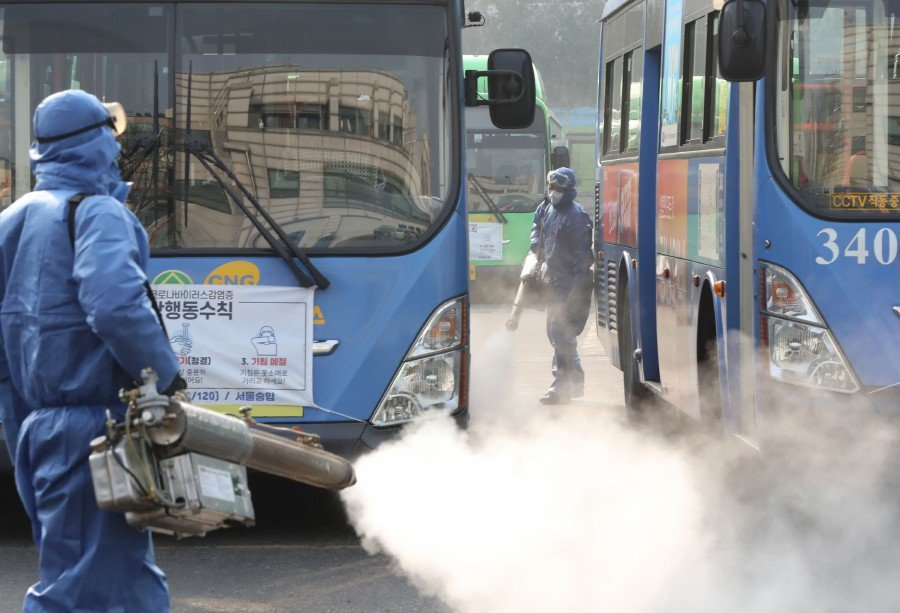 Workers from a disinfection service spray disinfectant as part of preventive measures against the spread of the COVID-19 coronavirus, at a public bus terminal in Seoul. -Yonhap/AFP
