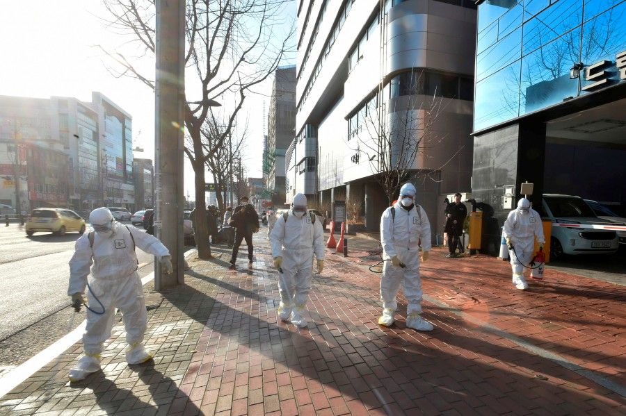 This handout picture taken on February 19, 2020 by Daegu Metropolitan City Namgu shows South Korean health officials wearing protective suit and spraying disinfectant in front of the Daegu branch of the Shincheonji Church of Jesus in the southeastern city of Daegu. -AFP/Daegu Metropolitan City Namgu