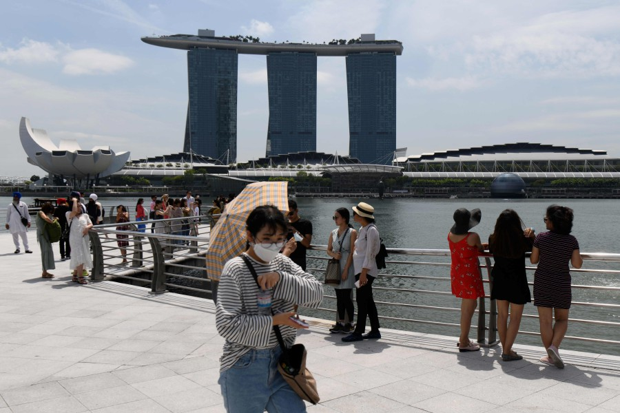 A visitor, wearing a protective facemask amid fears about the spread of the Covid-19 novel coronavirus, walks along Merlion Park in Singapore on February 17, 2020. (AFP)
