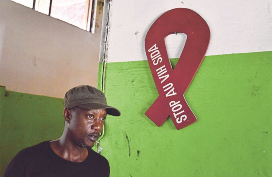 A man walks by a wooden red ribbon, the universal symbol of awareness and support for people living with HIV, at a press company in Abidjan, Ivory Coast.