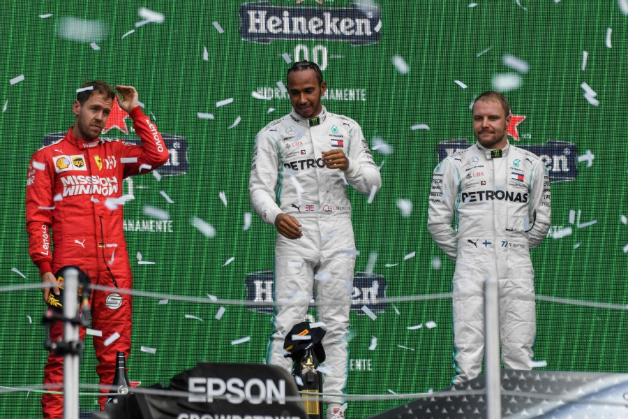 Mercedes' British driver Lewis Hamilton (C) celebrates on the podium after winning the F1 Mexico Grand Prix, next to runner-up Ferrari's Sebastian Vettel (L) and third-place Mercedes' Finnish driver Valtteri Bottas, at the Hermanos Rodriguez racetrack in Mexico City on October 27, 2019. - Lewis Hamilton won the Mexican Grand Prix on Sunday, but will have to wait for his sixth world title after Mercedes teammate Valtteri Bottas came home in third. (Photo by PEDRO PARDO / AFP)