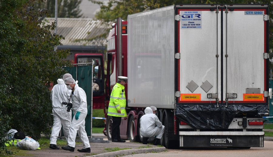 (FILES) In this file photo taken on October 23, 2019 British Police forensics officers work on lorry, found to be containing 39 dead bodies, at Waterglade Industrial Park in Grays, east of London, on October 23, 2019. - Investigators prepared on October 25 to start the first autopsies on the bodies of 39 people believed to be Chinese nationals found dead in a refrigerated truck, in a case that has shocked Britain. (Photo by Ben STANSALL / AFP)