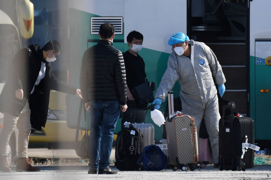 (FILES) This file photo taken on March 17, 2020 shows travellers and their bags disinfected as a preventive measure against the COVID-19 coronavirus before getting on a bus outside the New China International Exhibition Centre, near Beijing Capital Airport in Beijing. - Under pressure from anxious parents, Chinese citizens living in virus-hit Europe are flocking back home, with some even flying on private jets to escape the spiralling number of infections overseas. (Photo by GREG BAKER / AFP)