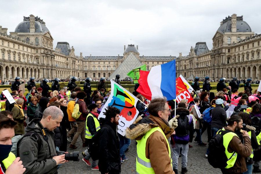 """Protesters take part in an anti-government demonstration called by the """"Yellow Vests"""" (Gilets Jaunes) as they walk past The Louvre Museum in Paris, on March 9, 2019. - """"Yellow Vests"""" protesters are taking to the streets for the 17th consecutive Saturday with a rallying dedicated on March 9, 2019 to the women's rights. This movement in France originally started as a protest about planned fuel hikes but has morphed into a mass protest against President's policies and top-down style of governing. AFP photo"""