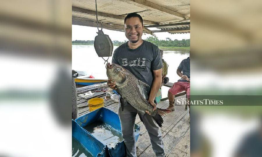 Muhammad Syazwan showing a Katla carp caught in Sungai Perak. -NSTP/Rosli Zakaria