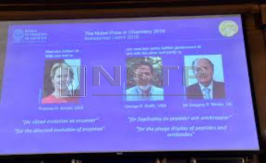 (File pix) A screen displaying portraits of Frances H. Arnold of the United States, George P. Smith of the United States and Gregory P. Winter of Great Britain during the announcement of the winners of the 2018 Nobel Prize in Chemistry. Jonas Ekstromer-AFP/Getty Images