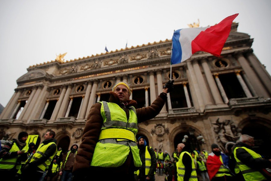 A man holding a French flag stands in front of the Opera during a Yellow Vest demonstration in Paris, France, 15 December 2018. EPA PIC