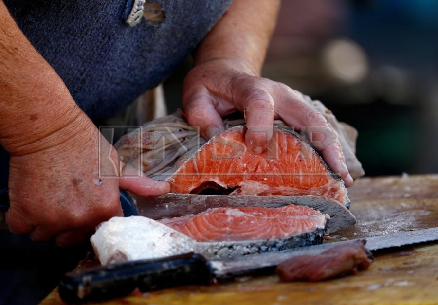(File pix) A fishmonger slices a fish at a fish market. Archive image for illustration purposes only. Reuters Photo