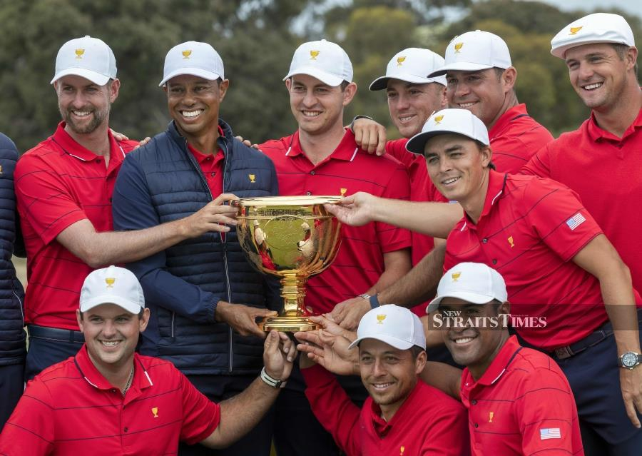 US team captain Tiger Woods (top row, 2nd L) and his teammates pose with the Presidents Cup after their win over the International Team on the final day of the Presidents Cup golf tournament in Melbourne. AFP