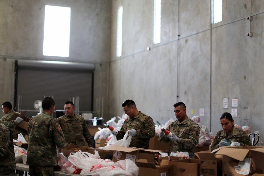 California National Guard troops package food bags to assist elderly volunteer workers in home confinement at FIND Food Bank during coronavirus disease (COVID-19) efforts in Indio, California, U.S., March 26, 2020. REUTERS/Lucy Nicholson