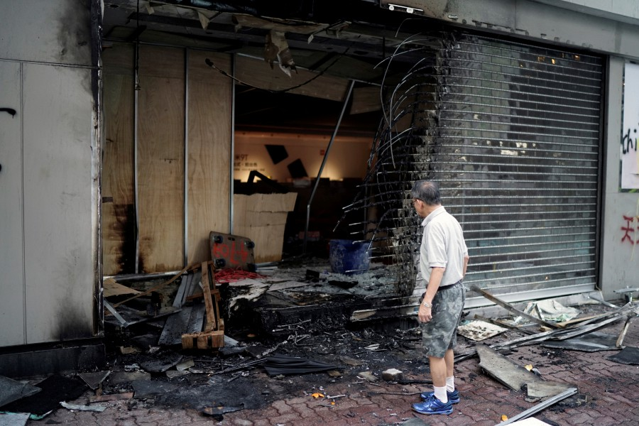 A man inspects a shop which was vandalised during Sunday's anti-government protest in Hong Kong, China. -- Reuters photo