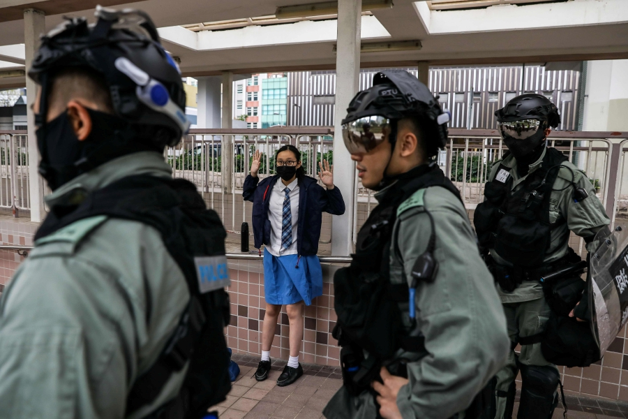 A school student is questioned by police in the Sai Wan Ho district in Hong Kong on November 11, 2019 following a day of pro-democracy protests. - A Hong Kong police officer shot at masked protesters -- hitting at least one in the torso -- during clashes broadcast live on Facebook, as the city's rush hour was interrupted by protests. (Photo by DALE DE LA REY / AFP)