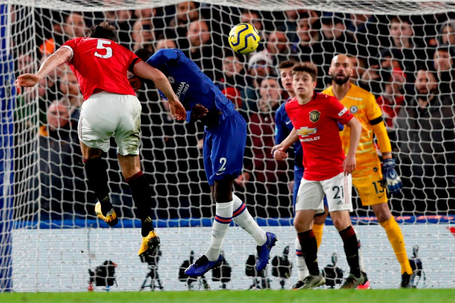 Manchester United's Harry Maguire (left) heads home their second goal against Chelsea at Stamford Bridge in London. -AFP