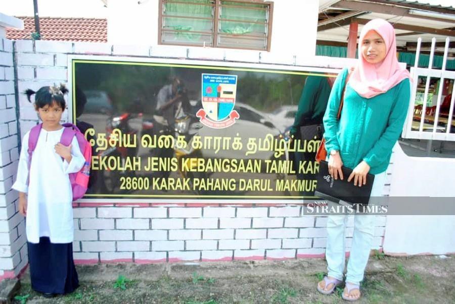 Nurul Fadznie Ashikin Hairul (right) sending her daughter Siti Nur Husna Alifdin on the first day of the school at SJKT Karak. - NSTP/Roselan Ab Malek