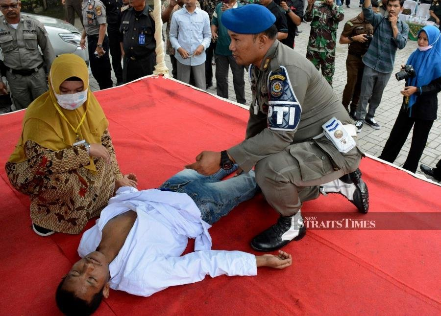 An Indonesian man faints after he was whipped in public on charges of engaging in sexual relations, in Aceh Timur on December 5, 2019. - Two Indonesian men and a woman were whipped in Indonesia's Aceh province after they were found guilty of having pre-marital sex, a serious crime under under the conservative region's Islamic law. AFP