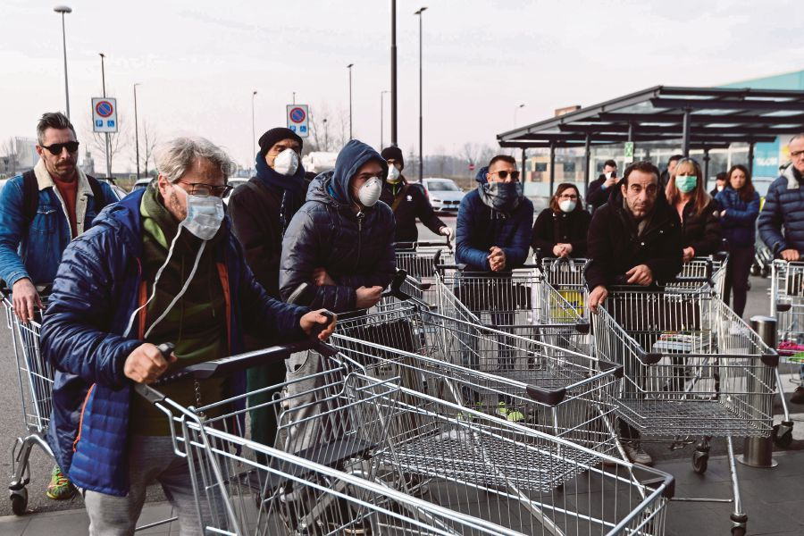 Residents wait to be given access to shop in a supermarket in small groups of forty people on February 23, 2020 in the small Italian town of Casalpusterlengo, under the shadow of a new coronavirus outbreak, as Italy took drastic containment steps as worldwide fears over the epidemic spiralled. (Photo by Miguel MEDINA / AFP)