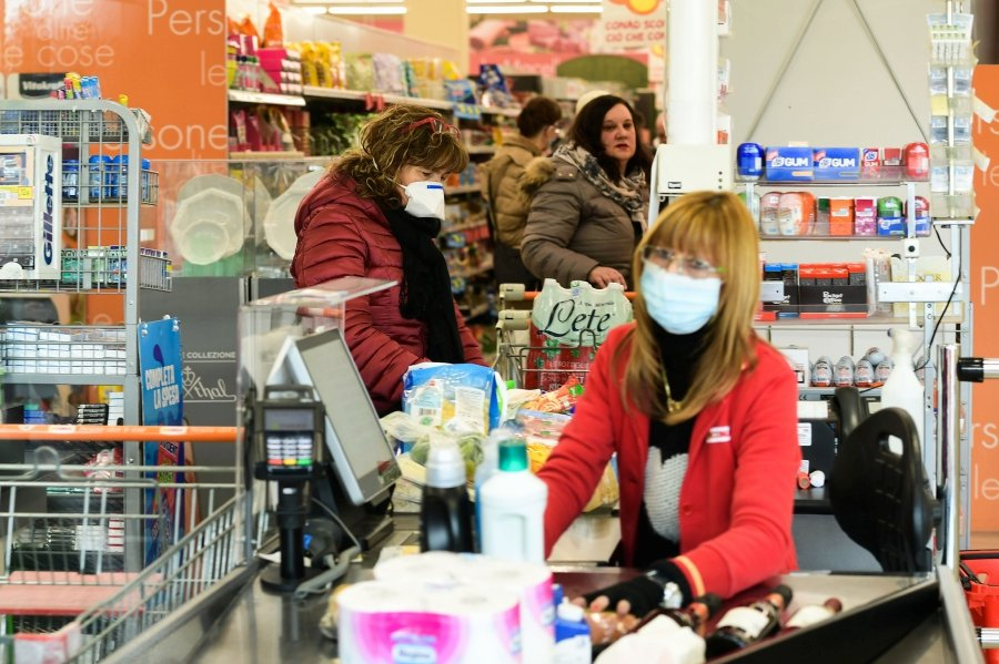 Residents wearing respiratory mask shop in a supermarket in small groups of forty people on February 23, 2020 in the small Italian town of Casalpusterlengo, under the shadow of a new coronavirus outbreak, as Italy took drastic containment steps as worldwide fears over the epidemic spiralled. (Photo by Miguel MEDINA / AFP)
