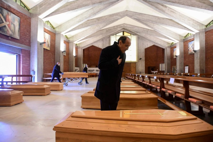 Parish priest of Seriate, Don Mario stands by one of the coffins stored into the church of San Giuseppe in Seriate, near Bergamo, Lombardy, on March 26, 2020, during the country's lockdown following the COVID-19 new coronavirus pandemic. (Photo by Piero CRUCIATTI / AFP)