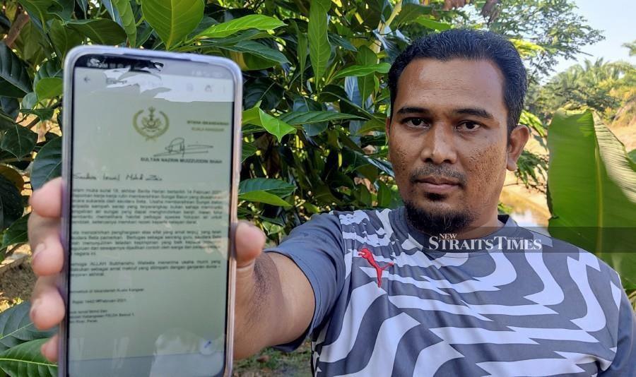 SK FELDA Besout 1 teacher, Ismail Mohd Zain shows a photo of the letter of appreciation by Sultan of Perak, Sultan Nazrin Shah. -NSTP/ROSMAN SHAMSUDIN.