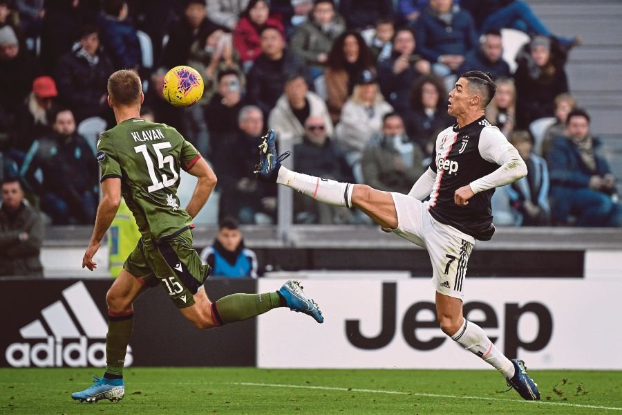 Juventus' Portuguese forward Cristiano Ronaldo (R) reaches out to the ball during the Italian Serie A football match Juventus vs Cagliari on January 6, 2020 at the Juventus Allianz stadium in Turin. (Photo by Marco Bertorello / AFP)
