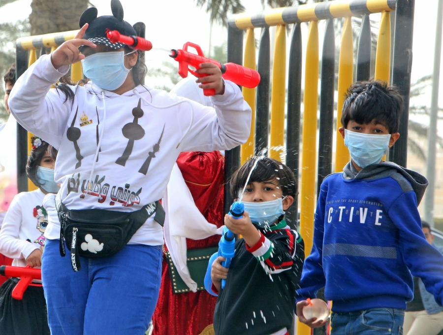 Kuwaiti children, wearing protective masks, play in Kuwait City on February 26, 2020 as they celebrate with others the country's 59th Independence Day and the 29th anniversary of the end of the Gulf war with the liberation of Kuwait from Iraqi occupation. - The new coronavirus hit four more Middle Eastern states, with Bahrain, Iraq, Kuwait and Oman reporting new cases and the UAE calling on its citizens not to travel to Iran and Thailand. Kuwait, for its part, called off celebrations for the Gulf state's national day, as it confirmed its first three cases of the virus, all connected to Iran. (Photo by YASSER AL-ZAYYAT / AFP)