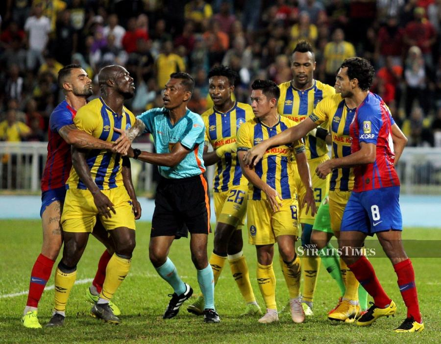 Pahang and JDT players argue with each other during Sunday's Super League match at the Darulmakmur Stadium. PIC BY FARIZUL HAFIZ AWANG