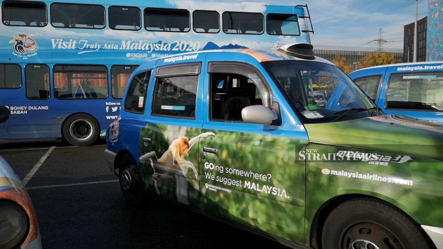 A London bus and taxi displaying Malaysian destinations.