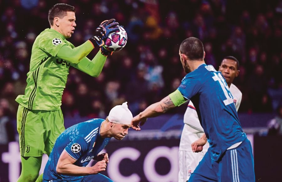 Juventus' Polish goalkeeper Wojciech Szczesny (L) grabs the ball during the UEFA Champions League round of 16 first-leg football match between Lyon and Juventus at the Parc Olympique Lyonnais stadium in Decines-Charpieu, central-eastern France, on February 26, 2020. (Photo by FRANCK FIFE / AFP)