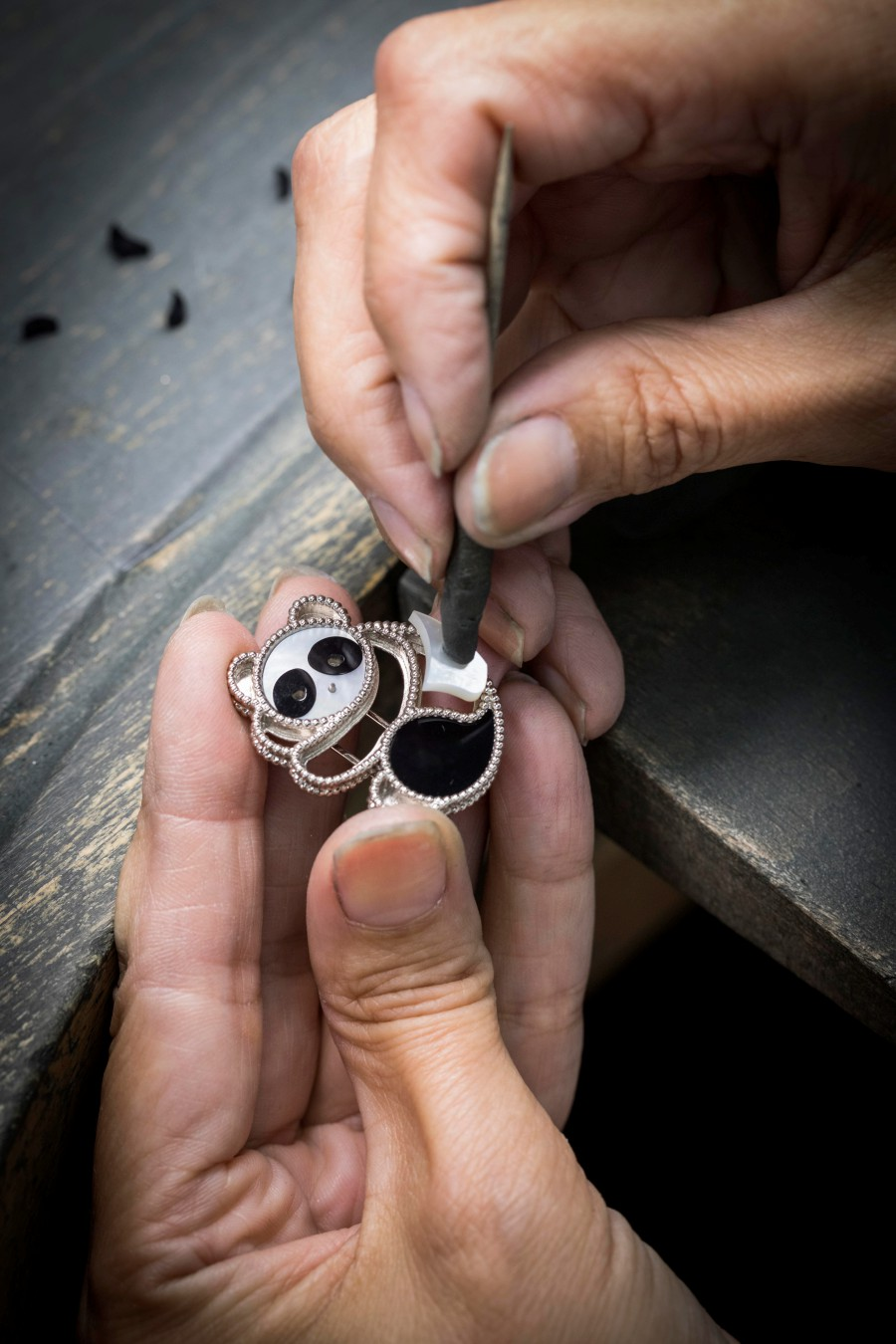 A Van Cleef & Arpels artisan fixing the mother-of-pearl onto the Panda clip.