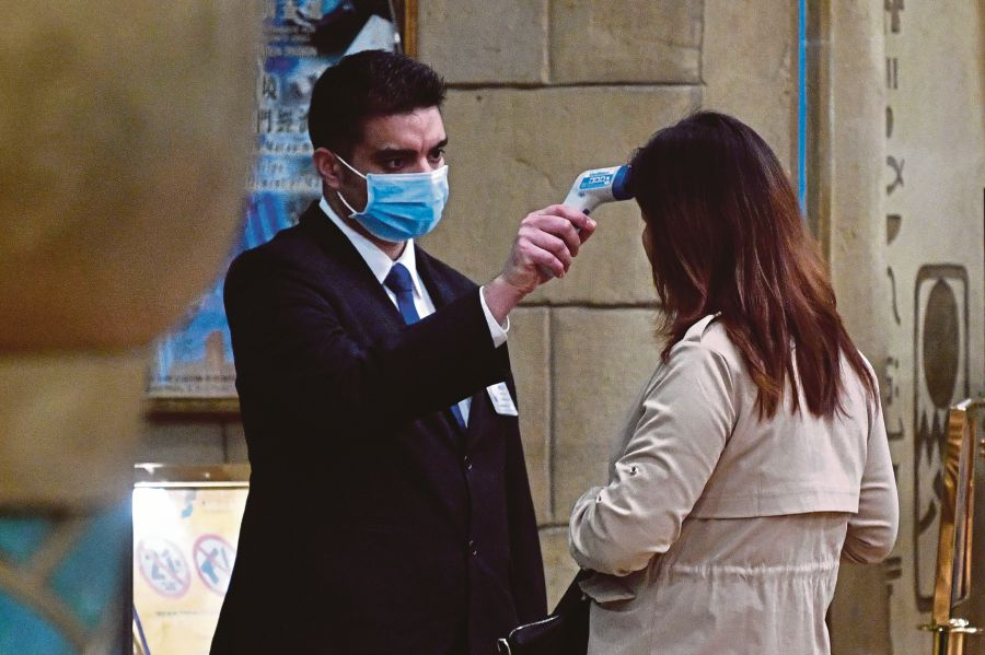 A staff member checks the temperature of a guest entering the New Orient Landmark hotel in Macau on January 22, 2020, after the former Portuguese colony reported its first case of the new SARS-like virus that originated from Wuhan in China. -AFP