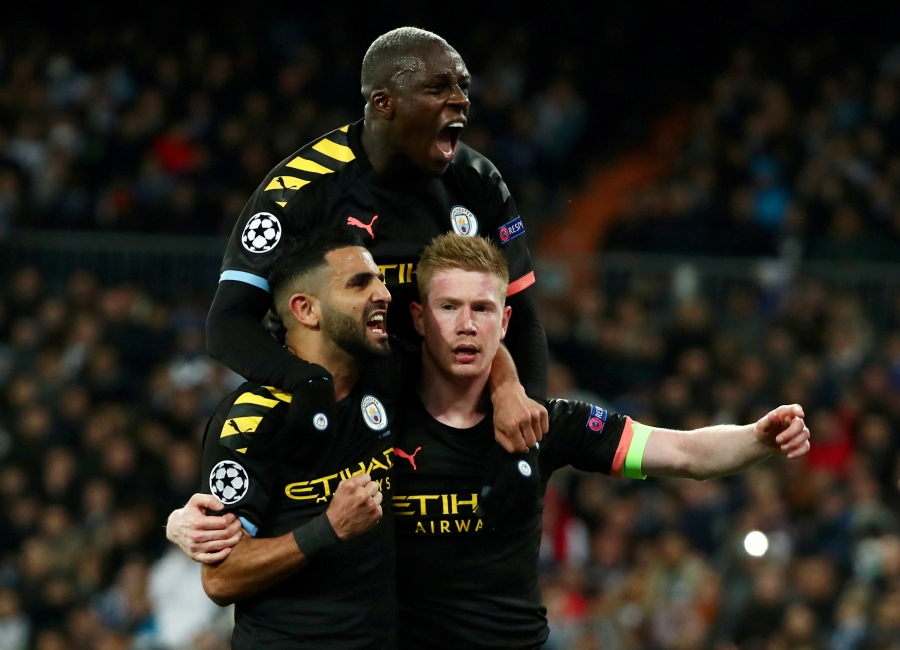 Champions League - Round of 16 First Leg - Real Madrid v Manchester City - Santiago Bernabeu, Madrid, Spain - February 26, 2020 Manchester City's Kevin De Bruyne celebrates scoring their second goal with Riyad Mahrez and Benjamin Mendy REUTERS/Sergio Perez
