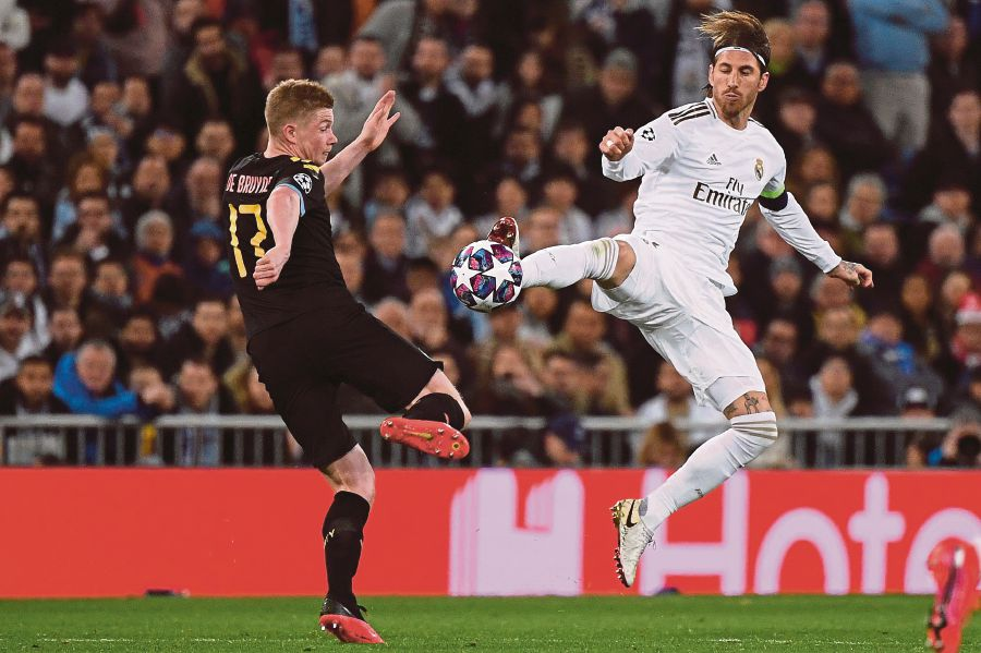 Real Madrid's Spanish defender Sergio Ramos (R) challenges Manchester City's Belgian midfielder Kevin De Bruyne during the UEFA Champions League round of 16 first-leg football match between Real Madrid CF and Manchester City at the Santiago Bernabeu stadium in Madrid on February 26, 2020. (Photo by PIERRE-PHILIPPE MARCOU / AFP)