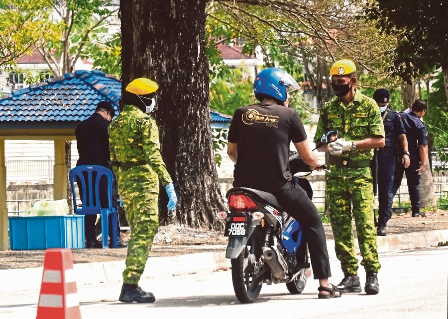 Malaysian soldiers and police inspect a motorist at a roadblock during the partial lockdown in Malaysia amid fears over the spread of the COVID-19 coronavirus, in Penang. -AFP pic