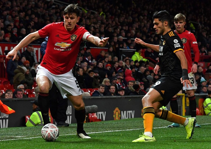Manchester United's English defender Harry Maguire (L) vies with Wolverhampton Wanderers' Mexican striker Raul Jimenez during the English FA Cup third round-replay football match between Manchester United and Wolverhampton Wanderers at Old Trafford in Manchester, north west England, on January 15, 2020. (Photo by Paul ELLIS / AFP)